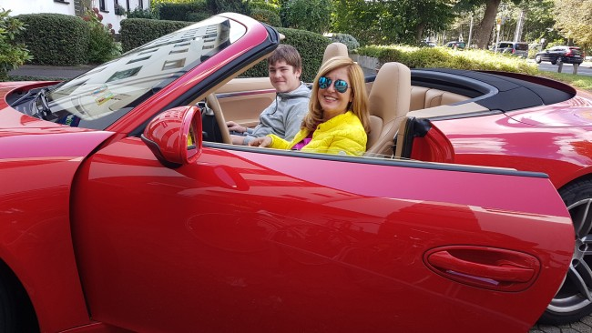 Nelly Kostadinova mit Schülerpraktikant Liam in ihrem roten Porsche